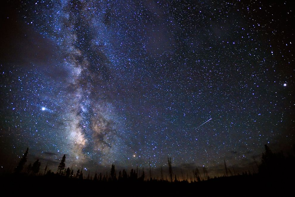 A meteor streaks through the night sky above Yellowstone National Park on Halloween 2008. PHOTOGRAPH BY JEFFREY BERKES